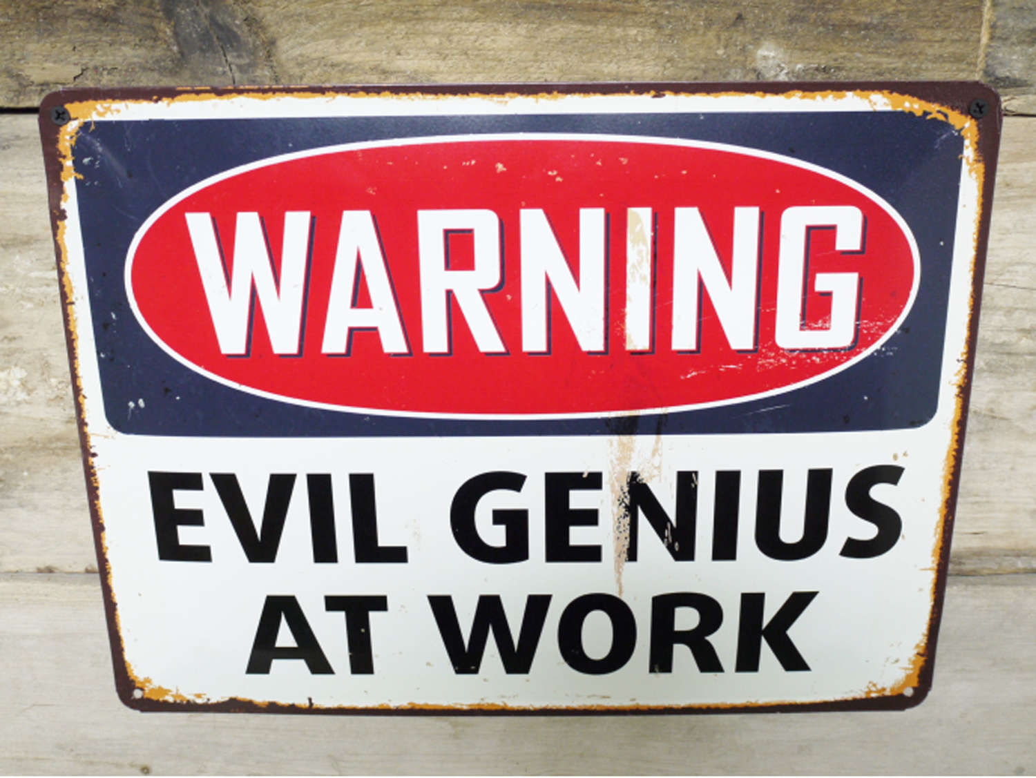 Metal wall hanging evil genius at work sign