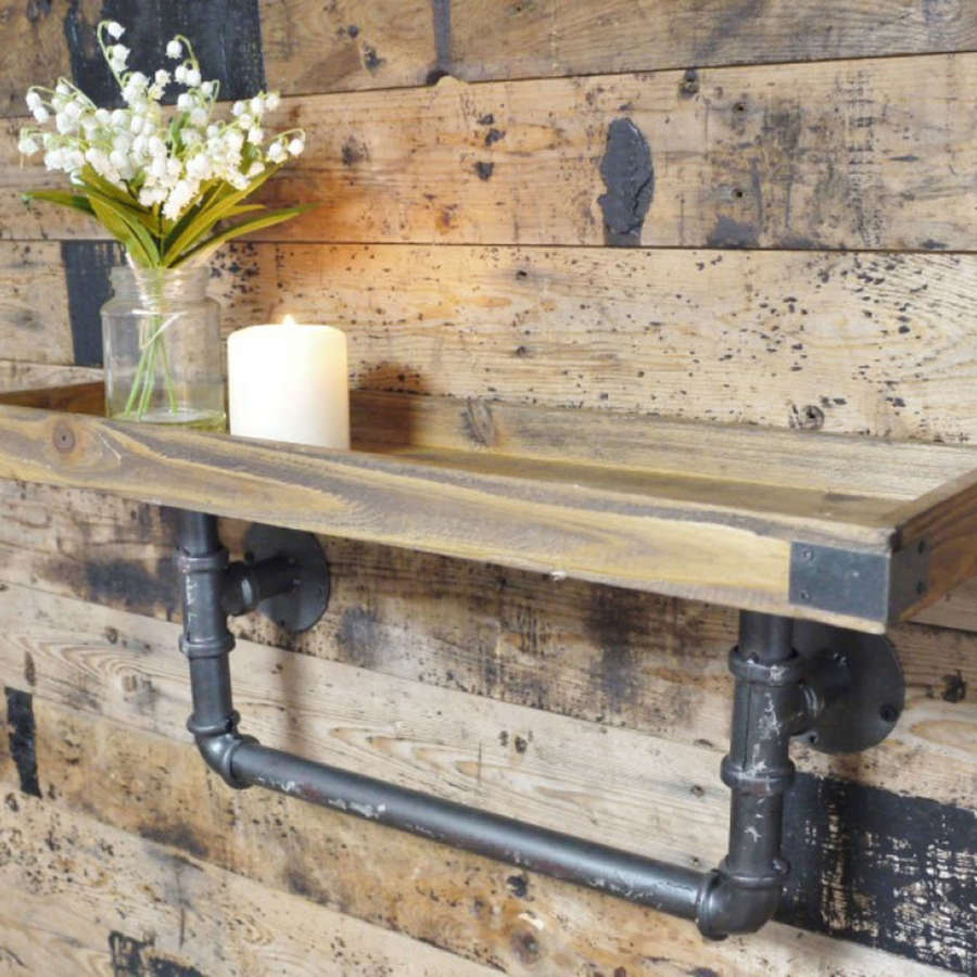 Rustic industrial wooden shelf with distressed effect iron pipework.