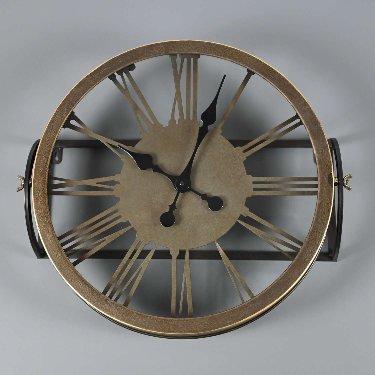 Round metal wall mounted clock with a bronze finish